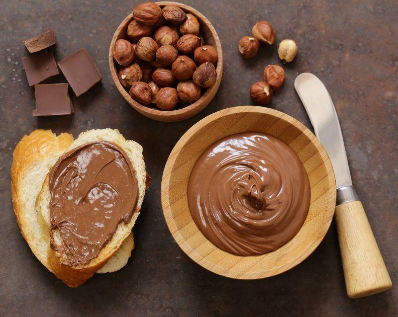 crema nocciole cioccolato fondente ciotola legno coltello fetta di pane