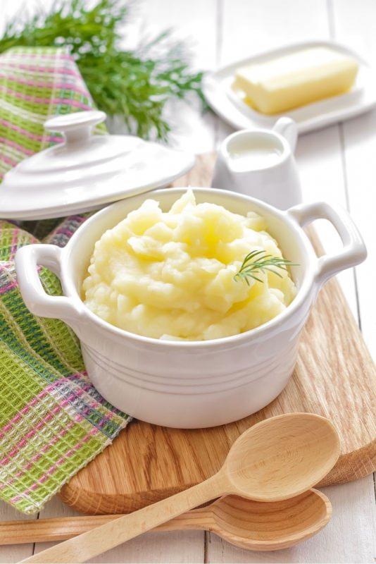 purè di patate ciotola ceramica bianca con coperchio su tagliere mestoli legno