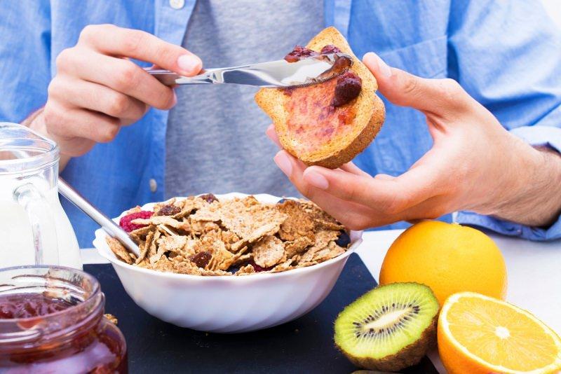 mani uomo spalmano marmellata su fetta biscottata colazione sana kiwi arancia