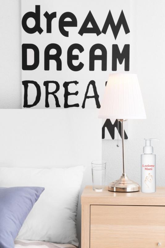 comodino vicino letto lume bicchiere acqua lozione mani scritta dream