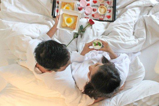 Quale regalo fare per San Valentino per lui e per lei toast uovo tegamino vassoio cuori caffelatte cappuccino rosa rossa letto coppia marito moglie amanti lenzuola federe bianche amore sorrisi accappatoio bianco capelli uomo donna castani