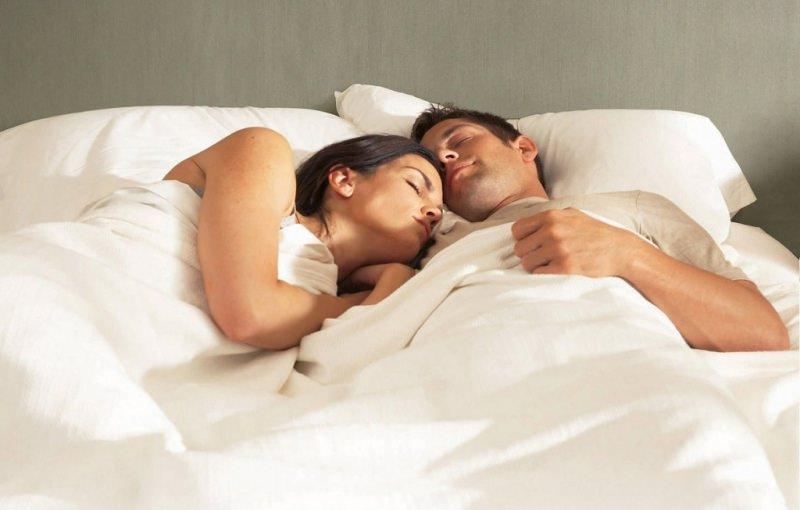 Vita di coppia: siete pronti a vivere insieme? cosa cambia veramente dormire al caldo sotto lenzuola coperte bianche donna uomo capelli castani serenità cuscini letto sonno