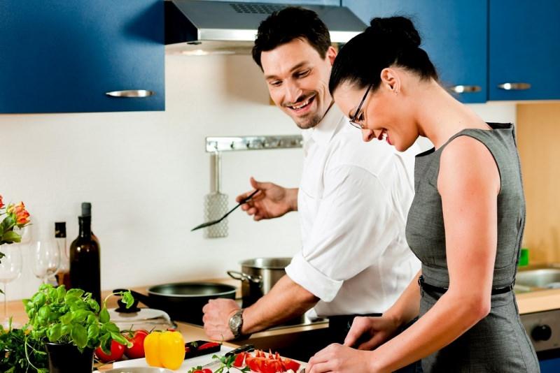 Vita di coppia: siete pronti a vivere insieme? cucinare cucina uomo sorriso pizzetto barba camicia bianca donna capelli castani legati chignon abito grigio occhiali ante blu pentole padella fornelli peperone giallo pomodoro coltelli