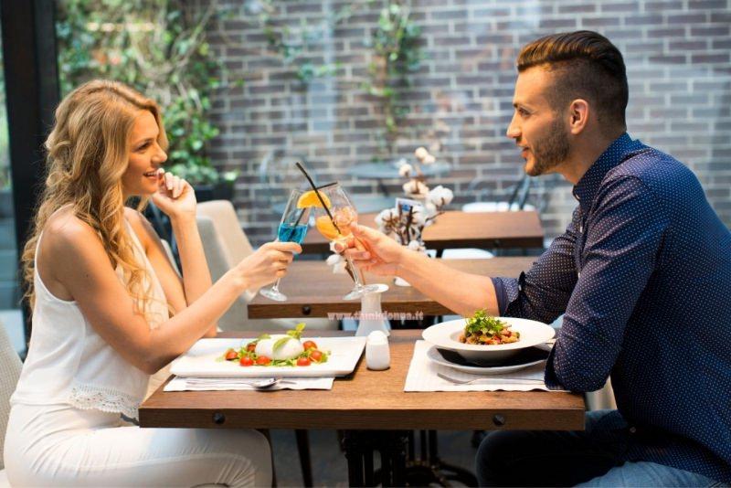 donna e uomo al primo appuntamento bar brindano drink incontro coppia