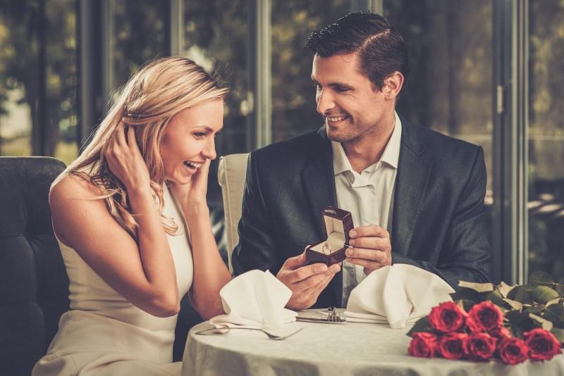 Quale regalo fare per San Valentino per lui e per lei regali proposta matrimonio anello fidanzamento oro astuccio cena romantica donna capelli lunghi lisci biondi sorriso sorpresa abito tubino bianco uomo capelli corti castano giacca blu camicia bianca bouquet mazzo rose rosse tovaglia tovagliolo bianco tavolo