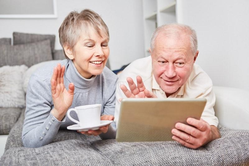 coppia anziani nonno nonna chattano tablet tazzina te caffè divani