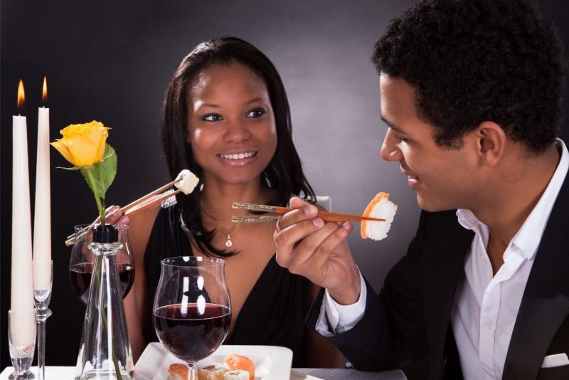 giovane coppia romantica donna uomo mangiano sushi lume luce candela