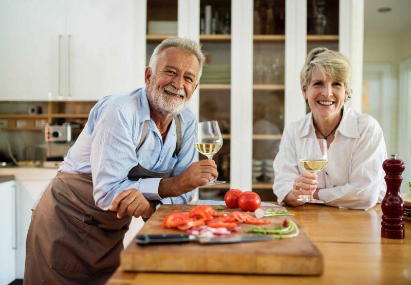 coppia uomo donna ancziani sorridenti cucina calici vino