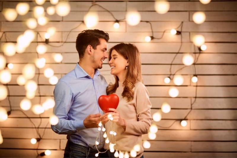 coppia innamorati con cuore in mano ghirlanda di luci San Valentino