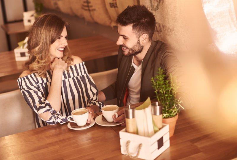 donna sorridente seduta al bar uomo seduzione incontro caffè conquistare