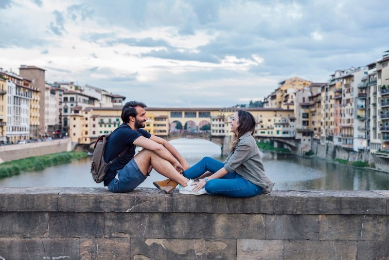 coppia innamorati uomo donna seduti davanti ponte vecchio firenze arno fiume
