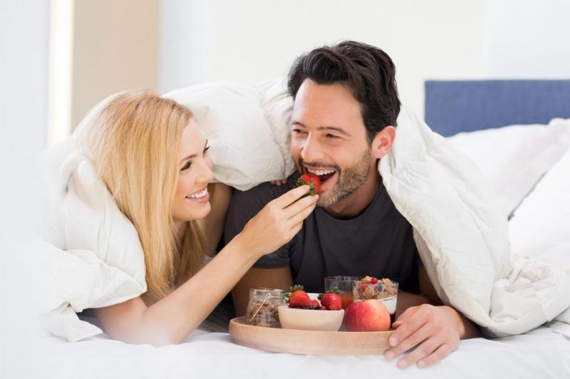 coppia innamorati donna uomo mangiano fragole a letto cibo afrodisiaco sorrisi