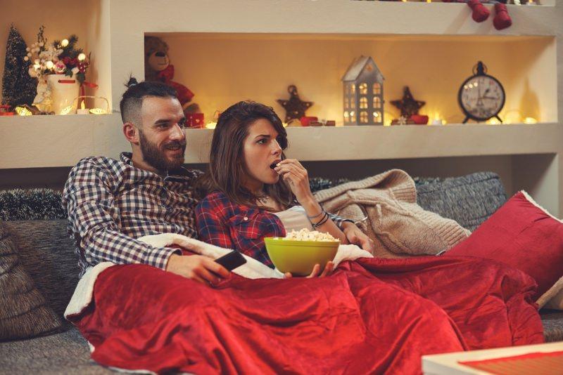 coppia uomo donna maniano popcorn mentre guardano TV divano soggiorno luci