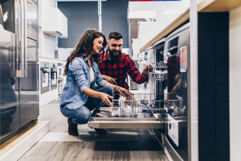 Coppia nel negozio di elettrodomestici lavastoviglie grandi frigorifeto uomo donna