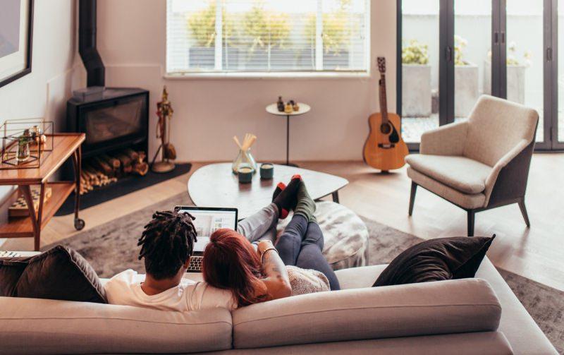coppia sul divano stare insieme a casa soggiorno relax guarda laptop notebook