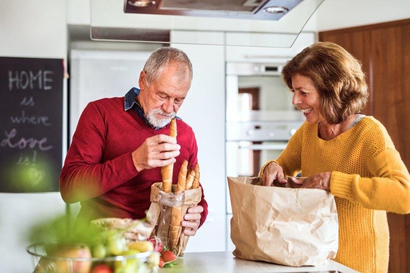 coppia anziani sistema spesa in cucina sacchetti pane frutta e verudra sorriso