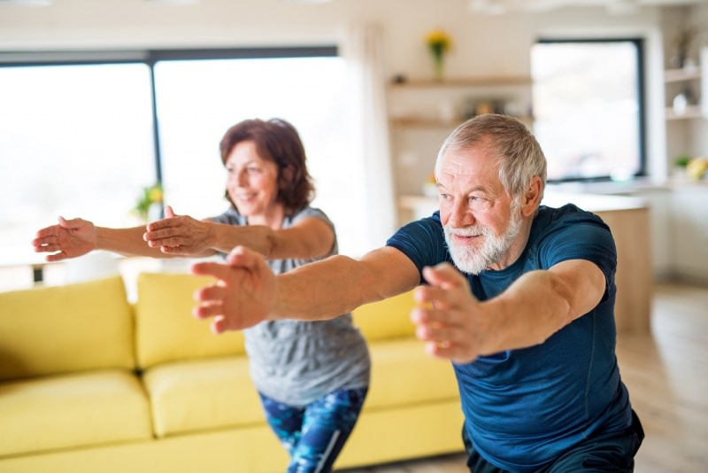 coppia uomo donna anziani fanno esercizi fisici fitness resto a casa