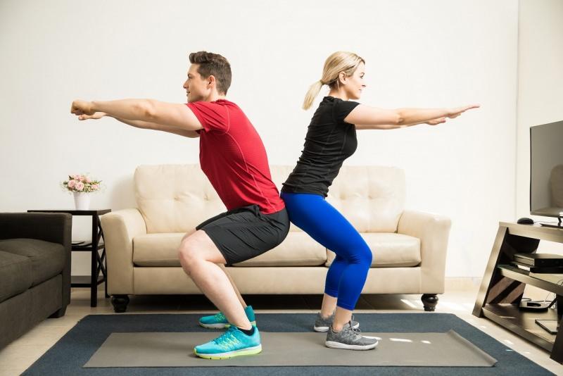donna e uomo fanno squat in soggiorno davanti divano resto a casa