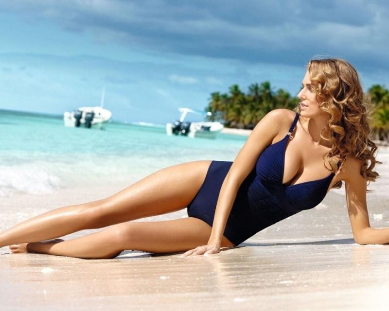 Estate 2018: i costumi interi che valorizzano al meglio i punti giusti mare donna sdraiata spiaggia sabbia acqua onde costume intero blu capelli lunghi morbidi bondi ondulati