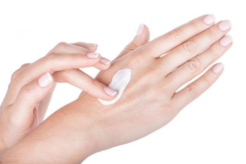 donna spalma crema sul dorso della mano ben curata