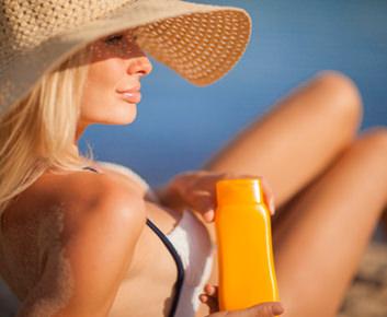 Come applicare la crema solare viso donna capelli biondi profile sorriso occhi azzurri cappello paglia mare costume da bagno intero bianco blu flacone lozione protezione sole