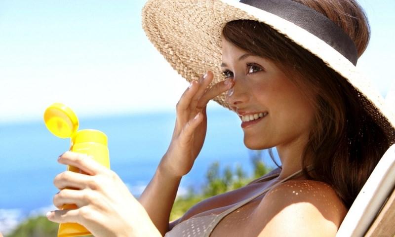 Come applicare la crema solare viso donna protezione cappello paglia capelli occhi castani sorriso mette lozione nazo sorriso denti bianchi bikini beige mare onde acqua azzurra flacone estate sole