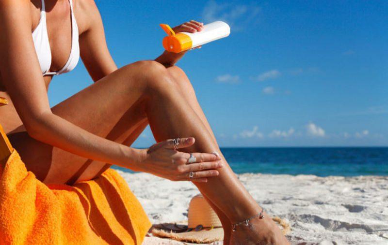 Come applicare la crema solare protezione sole corpo donna bikini reggiseno bianco sdraio legno telo spugna arancione mano anelli cappello paglia sabbia cavigliera spalma lozione flacone mare onde cielo azzurro sole
