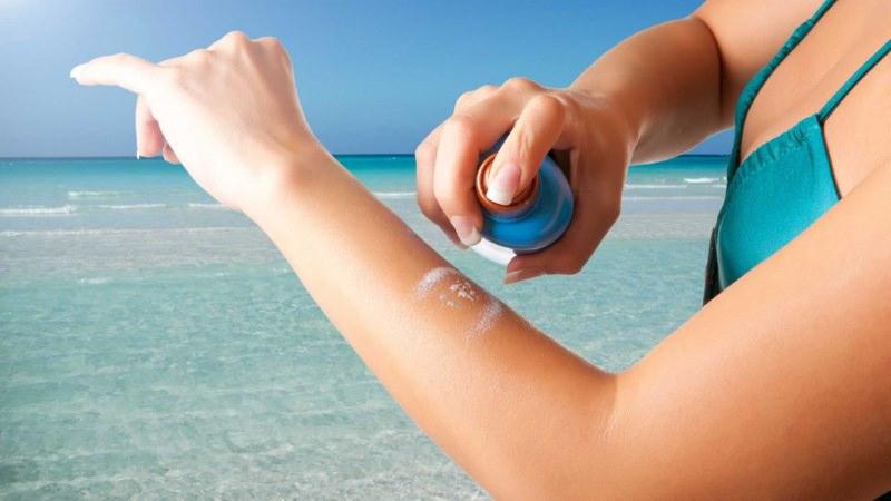 Come applicare la crema solare braccia mani spray protezione tintarella abbronzatura mare onde acqua azzurra limpida corpo donna bikini reggiseno turchese sole