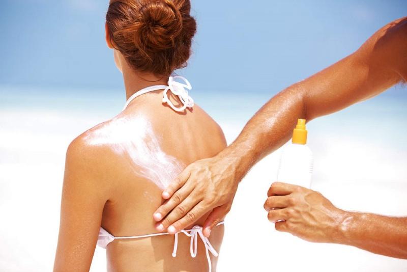 Come mettere la protezione solare sulla schiena? applicare mano uomo spalma crema spalle donna bikini bianco capelli castani legati chignon spiaggia sabbia mare