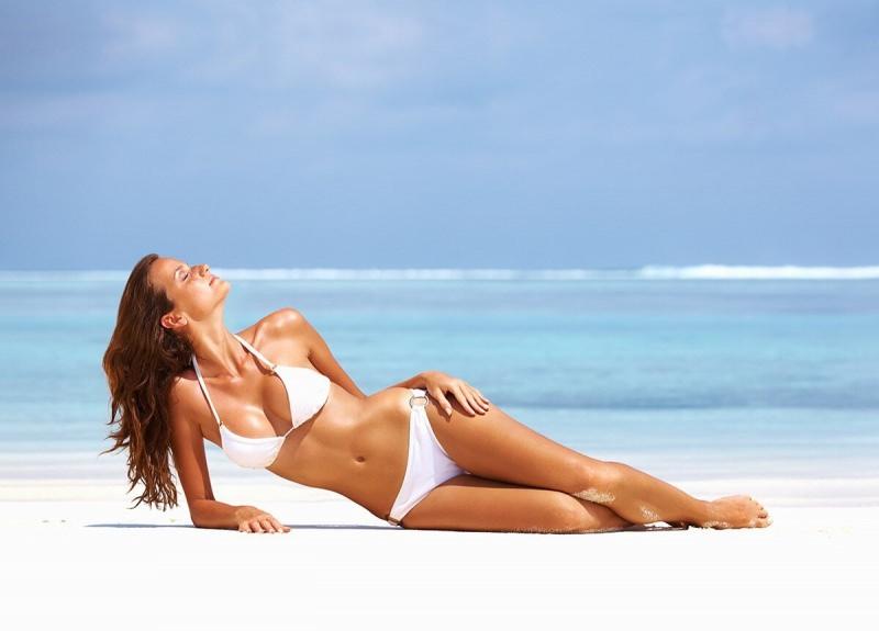 Come applicare la crema solare protezione sole estate spiaggia sabbia mare onde acqua azzurra corpo bella donna snella bikini reggiseno triangolo bianco abbornzatura tintarella capelli lunghi castani