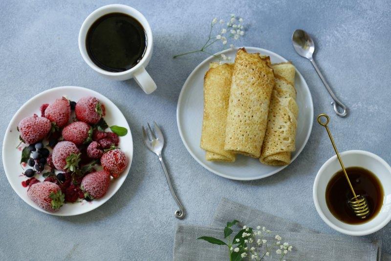 crêpes arrotolate ciotola frutta fragole mirtilli zucchero tazzina caffè spargi miele
