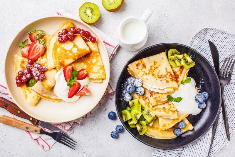 crêpes dolci con frutta mirtilli kiwi fragole ribes panna zucchero a velo piatto padella