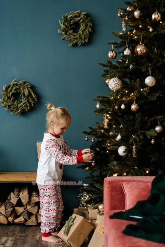 bambina decora albero di natale palline decorazioni natalizi regali legno divano velluto rosa luci
