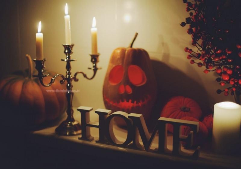 halloween decorazioni interni camino candelabro candele accese scritta home zucca