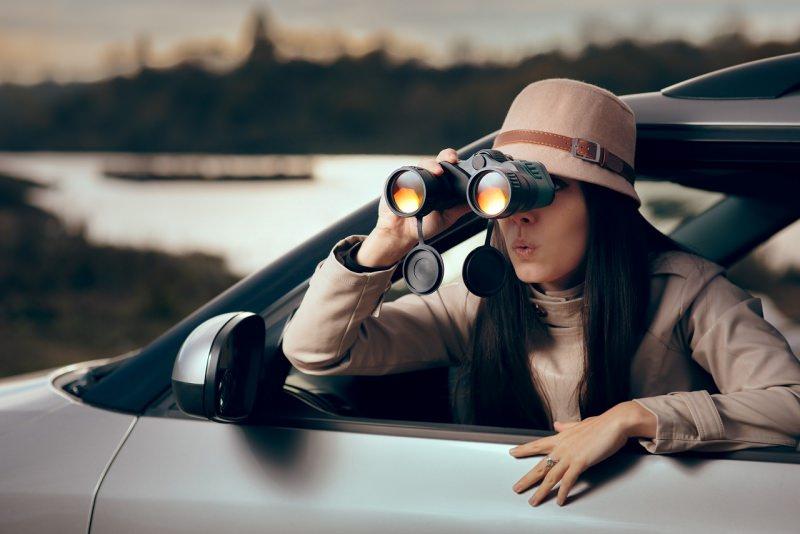 donna detective con binocolo auto investigazione privata