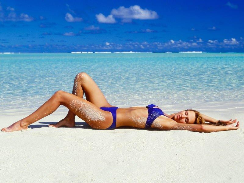 donna fisico snello sdraiata spiaggia mare estate azzurro bikini blu due pezzi sabbia acqua limpida azzurra bella capelli biondi occhi chiusi mani cosce fianchi dieta dimagrante detox