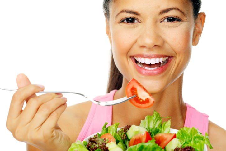 donna occhi castani capelli raccolti coda di cavallo sorriso denti bianchi mangiare verdure insalata pomodori lattuga radicchio cetriolo forchetta pomodoro dieta detox rimodellante disintossicante