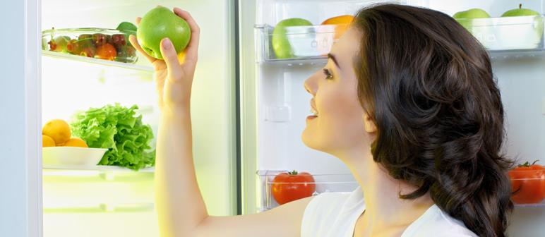 dieta detox frigorifero donna sorridente sorriso capelli castani frutta verdure insalata pomodoro mela maglietta bianca