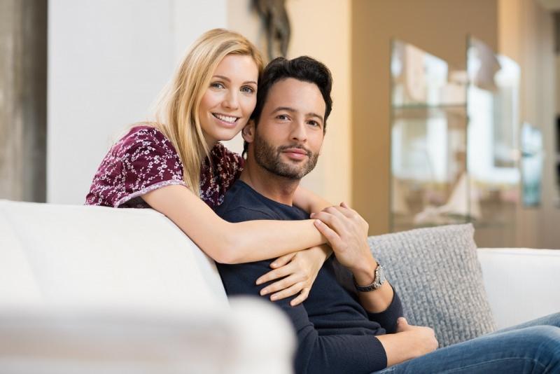 giovane coppia sorridente innamorata abbracciata sul divano