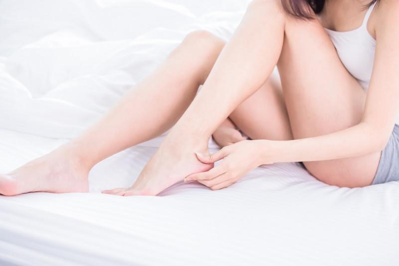 corpo donna sul letto massaggia piede dolore