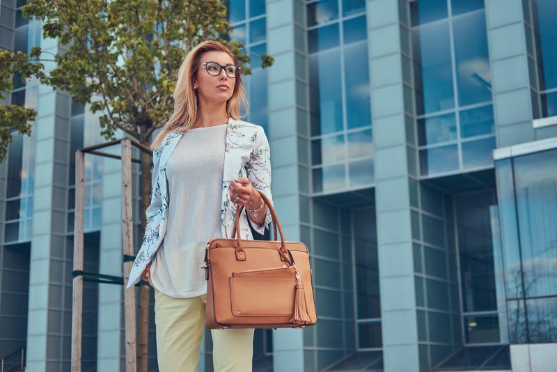 giovane donna elegante maglietta giacca a fiori pantalone pastello borsa classica occhiali