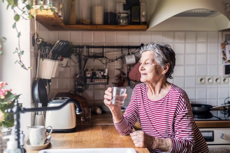 donna anziana beve bicchiere acqua davanti finestra cucina ondata di calore