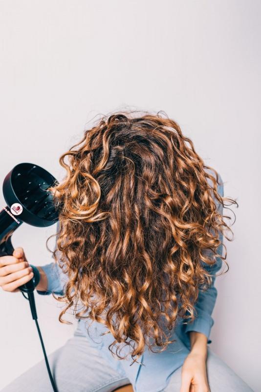 donna asciuga i capelli ricci con phon e diffusore