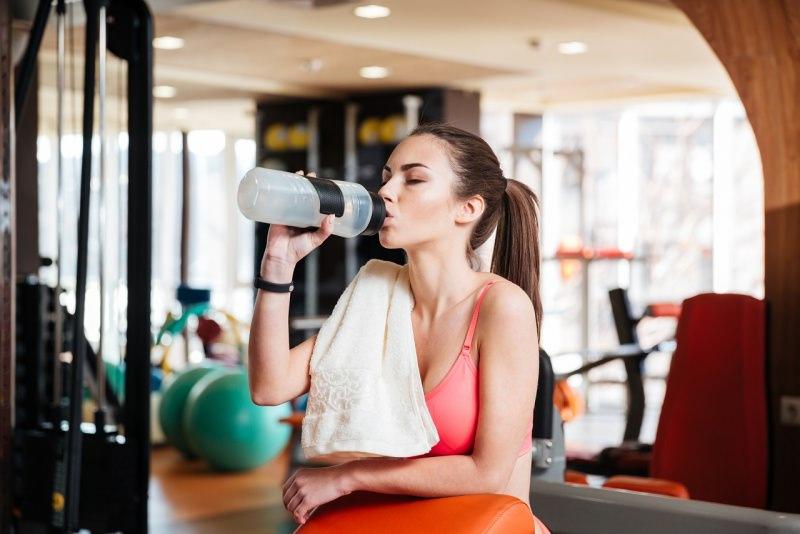 donna atletica si idrata in palestra beve integratore