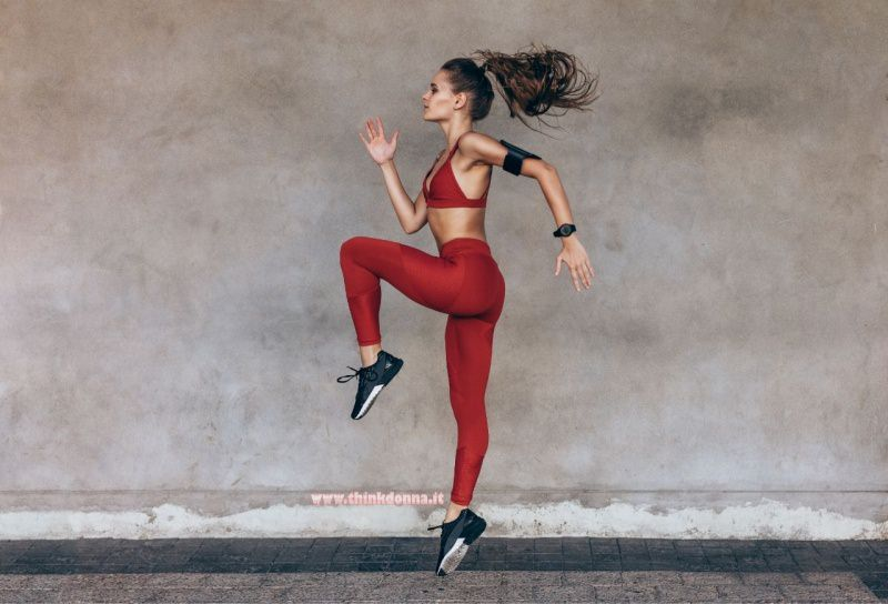 giovane donna atletica salto leggins tenuta fitness