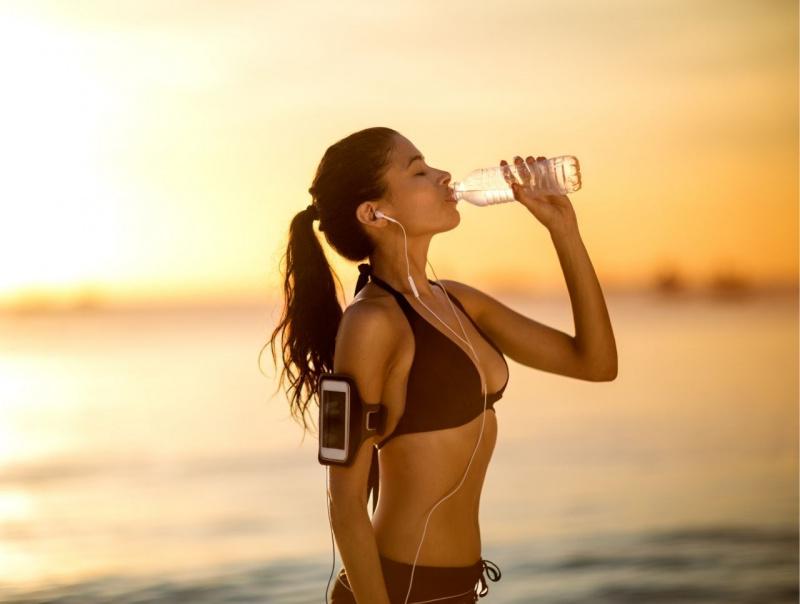 bella donna atletica beve acqua da bottiglia al mare al tramonto