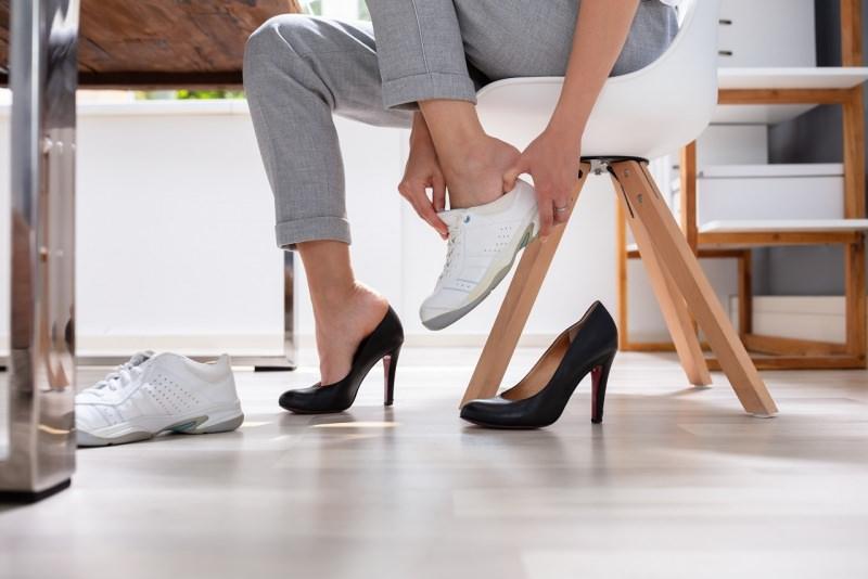 donna cambia scarpe con tacco alto in ufficio con sneackers bianche