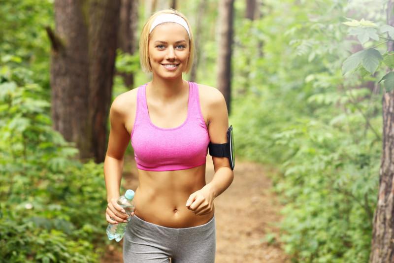 giovane e bella donna cammina foresta abbigliamento fitness bottiglia acqua sorriso