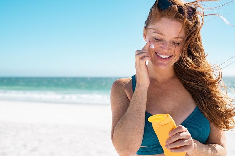 protezione solare bella donna sorriso tipo nordico fototipo 2 lentiggini capelli rossi mare estate crema