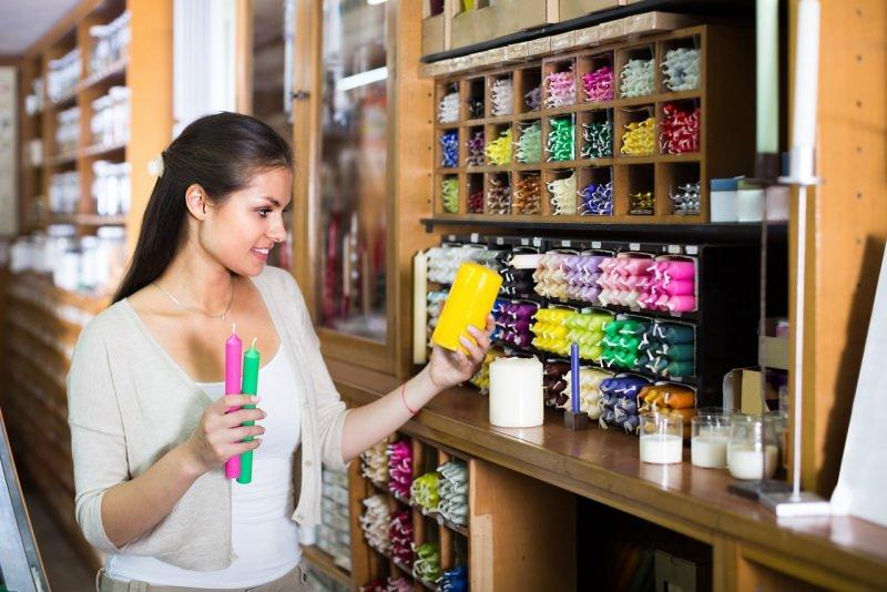 negozio candele shopping donna guarda candela colorata gialla